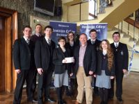 Teacher Ian Hynds and senior prefects present Aodh O'Loan with a cheque for SFR.